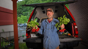 A grower holding fresh radishes in each hand while standing in front of his open pickup truck bed at a farmers market